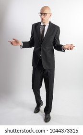 Full length portrait of a slim tall bald man in a black suit with black tie with his arms apart. The expression of question and bewilderment. White background.