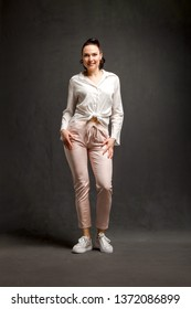 full length portrait of smiley stylish woman over grey background