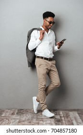 Full length portrait of a smiling african man in sunglasses holding jacket over shoulder and typing message on mobile phone isolated over gray background