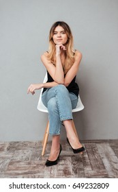 Full length portrait of a smiling attractive girl sitting on a chair with legs crossed and looking at camera isolated over grey background