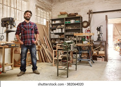 Full length portrait of a smiling bearded crafstman, standing proudly in his workshop, with heavy-duty machinery for woodwork