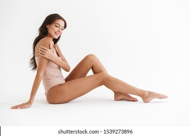 Full length portrait of a smiling beautiful sensual young brunette woman wearing swimsuit sitting isolated over white background, posing