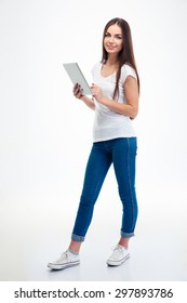 Full length portrait of a smiling beautiful woman holding tablet computer isolated on a white background. Looking at camera