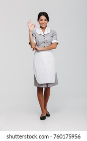 Full length portrait of smiling beautiful housekeeper in uniform showing OK gesture while standing and looking at camera, isolated on white background