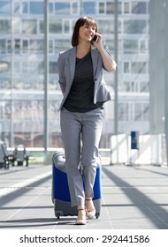 Full length portrait of a smiling business woman talking on mobile phone at airport