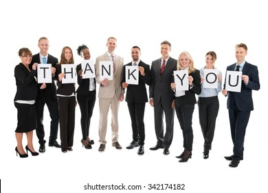 Full length portrait of smiling business team holding Thank You sign against white background