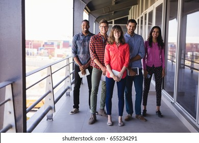 Full length portrait of smiling business people standing in balcony