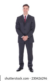 Full length portrait of smiling businessman with hands clasped standing against white background