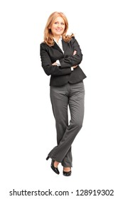 Full length portrait of a smiling businesswoman leaning on wall isolated on white background