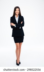 Full length portrait of a smiling businesswoman standing with arms folded isolated on a white background. Looking at camera