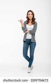 Full length portrait of a smiling casual girl standing and pointing finger away isolated over white background