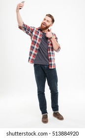 Full length portrait of a smiling casual man taking selfie and showing thumbs up gesture over white background