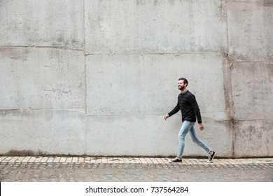 Full length portrait of a smiling casual man walking on a city street against gray wall