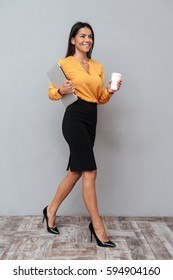 Full length portrait of a smiling confident business woman holding laptop and cup of coffee over gray background