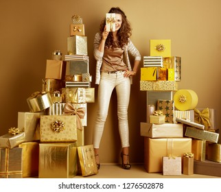 Full length portrait of smiling elegant woman in gold beige clothes among 2 piles of golden gifts in front of a plain wall holding gift box hiding half of the face. birthday illustration.