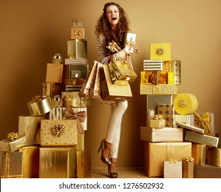 Full length portrait of smiling elegant woman in gold beige clothes with gifts and shopping bags among 2 piles of golden gifts in front of a plain wall. abundance of gifts for everyone. deals, sales