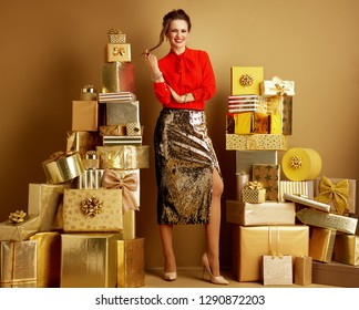 Full length portrait of smiling elegant woman in red blouse and golden sparkly sequin pencil skirt among 2 piles of golden gifts in front of a plain wall. Valentine's Day. deals, sales, discounts