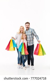 Full length portrait of a smiling family holding paper shopping bags isolated over white background