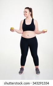Full length portrait of a smiling fat woman choosing between donut and apple isolated on a white background