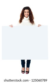 Full length portrait of a smiling female displaying blank whiteboard.