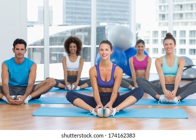 Full length portrait of smiling fit class doing the butterfly stretch in exercise room