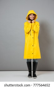 Full length portrait of a smiling girl dressed in raincoat and rubber boots posing with hood on her head and looking at camera isolated over gray background
