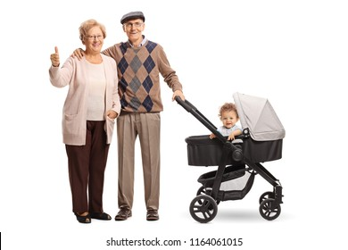 Full length portrait of smiling grandparents with a stroller and a baby showing thumbs up isolated on white background