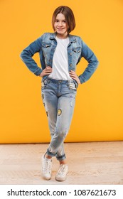 Full length portrait of a smiling little schoolgirl standing with hands on hips over yellow background