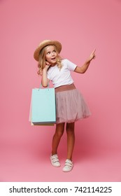 Full length portrait of a smiling little girl in hat and skirt holding shopping bags while standing and pointing finger away isolated over pink background