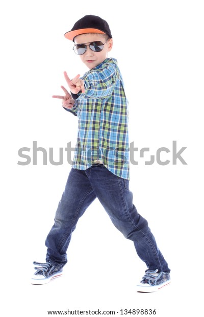 Full length portrait of smiling little boy in jeans cup and sunglasses on white background