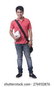 Full length portrait of smiling male student with books and bag against white background