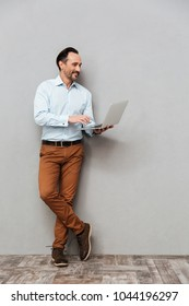 Full length portrait of a smiling mature man dressed in shirt using laptop computer while standing over gray background