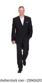 Full length portrait of smiling mature businessman walking over white background