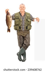 Full length portrait of a smiling mature fisherman holding a fish next to a panel isolated on white background