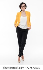 Full length portrait of a smiling pretty woman in eyeglasses and a jacket posing while standing and looking at camera isolated over white background