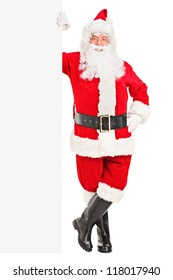 Full length portrait of a smiling Santa Claus posing next to a billboard isolated on white background
