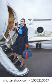 Full length portrait of smiling stewardess with luggage standing on stairs near aircraft. Occupation concept