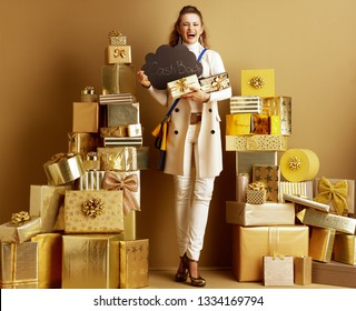 Full length portrait of smiling stylish fashion-monger in white clothes among 2 piles of golden gifts in front of a plain wall showing present boxes and CashBack sign. Cashback this Holiday Season.