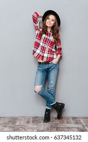 Full length portrait of a smiling stylish woman in plaid shirt standing and posing isolated over gray background