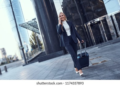 Full length portrait of a smiling successful businesswoman pulling suitcase and talking on the phone in the city.