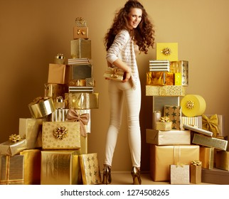 Full length portrait of smiling trendy woman in gold beige clothes among 2 piles of golden gifts in front of a plain wall holding present box. first minute shopping with huge gift opportunities