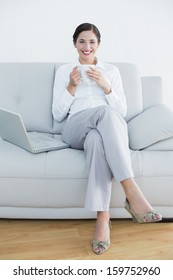 Full length portrait of a smiling well dressed young woman with laptop and coffee cup on sofa at home