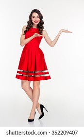 Full length portrait of a smiling woman in red dress holding copyspace on the palms isolated on a white background