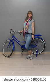 Full length portrait of a smiling woman standing near a blue bicycle. Looking at camera