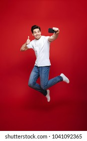 Full length portrait of a smiling young man in white t-shirt showing thumbs up gesture while taking a selfie and jumping isolated over red background