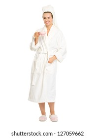 Full length portrait of smiling young woman in bathrobe with cup of coffee