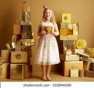 Full length portrait of smiling young girl in beige fit and flare dress and a little crown on head with golden gift card among 2 piles of golden gifts in front of a plain wall. unique birthday gifts.