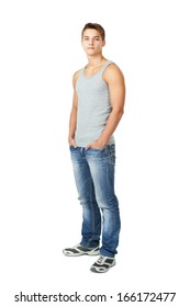 Full length portrait of smiling young man standing with hands in pockets isolated on white background