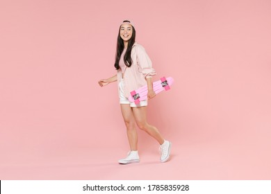 Full length portrait of smiling young asian girl in casual clothes, cap isolated on pastel pink background studio portrait. People lifestyle concept. Mock up copy space. Hold skateboard looking aside