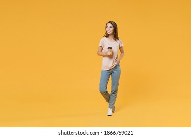 Full length portrait of smiling young brunette woman 20s wearing pastel pink casual t-shirt posing hold paper cup of coffee or tea looking aside isolated on bright yellow color wall background studio